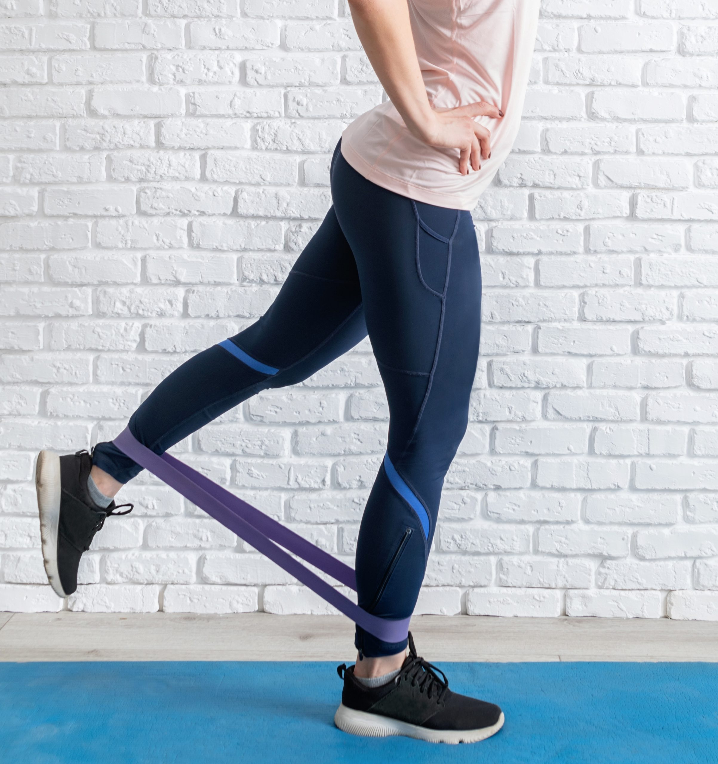 Stay home. Home fitness. A woman exercising legs at home using rubber resistance band